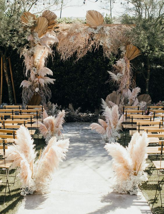 a boho wedding space with a boho wedding arch decorated with pampas grass, other grasses and fronds plus pampas grass lining up the aisle