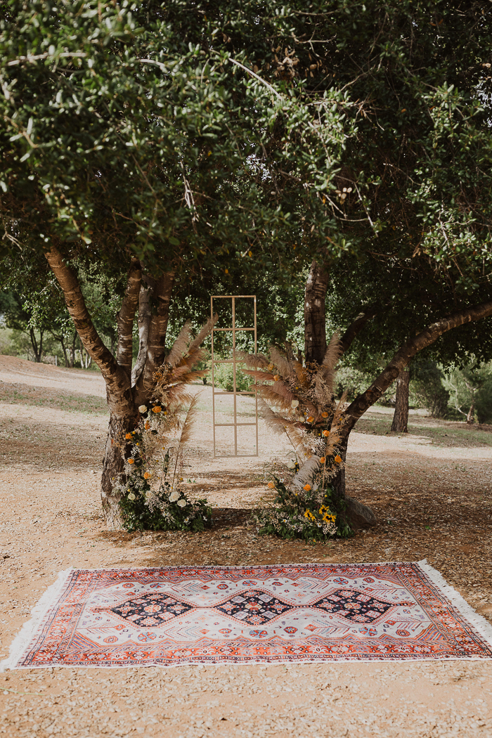 a boho wedding was done with living trees decorated with greenery, white and mustard blooms and pampas grass