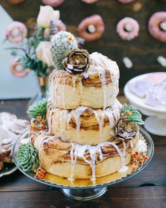 a cinnamon roll wedding cake of three tiers, with white icing, cacti and succulents on top for a creative wedding