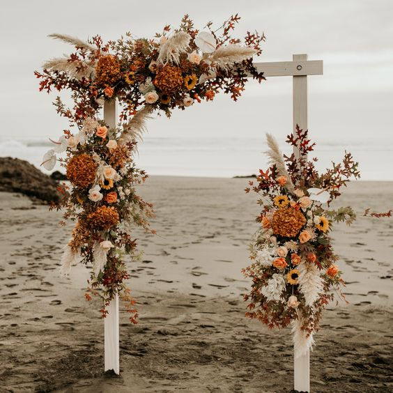 a fall wedding arch with orange, rust blooms, pampas grass and bright fall leaves is a statement