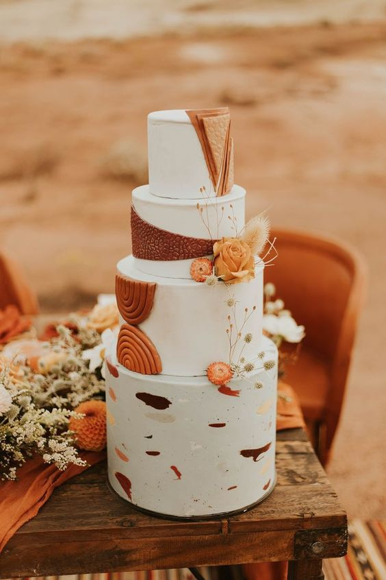 a fantastic boho wedding cake with white tiers, colorful brushstrokes, rust sugar detailing and some orange and dried blooms