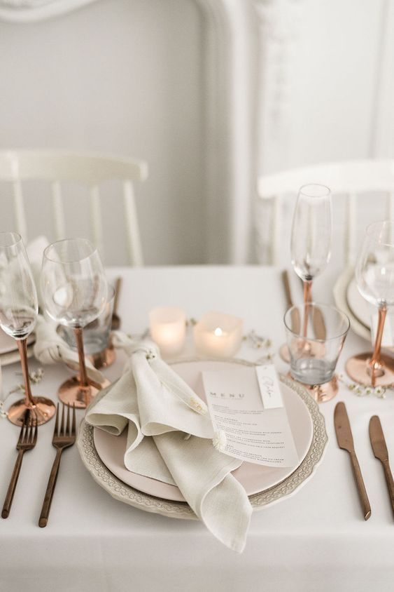 a lovely and airy Scandinavian wedding tablescape with copper cutlery and glasses, candles, neutral linens and plates