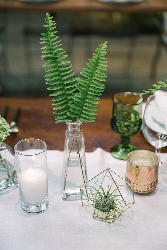 06 a modern urban jungle wedding centerpiece of a vase with fern leaves, succulents in a hexagon cover and candles is very cool