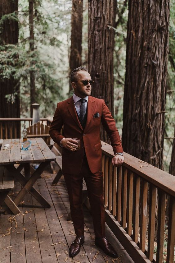 a rust suit, a black vest, a grey tie, brown shoes for a super elegant and statement groom's look at a fall wedding