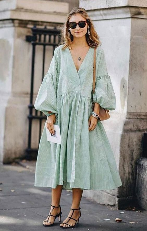 a statement green oversized midi dress with puff sleeves, a deep neckline, black shoes, statement earrings