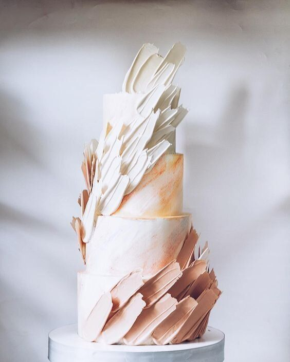 a statement wedding cake with watercolor tiers and white and blush brushstrokes is a very chic and beautiful idea