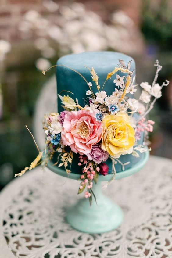 a teal wedding cake with bold and pastel blooms plus dried ones, dried herbs and foliage is a stylish and bold idea