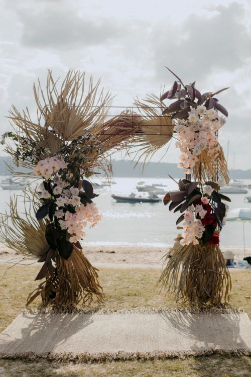 a bold and eye-catchy boho wedding arch with dried fronds, blush blooms and dark leaves is a very stylish idea for a boho wedding