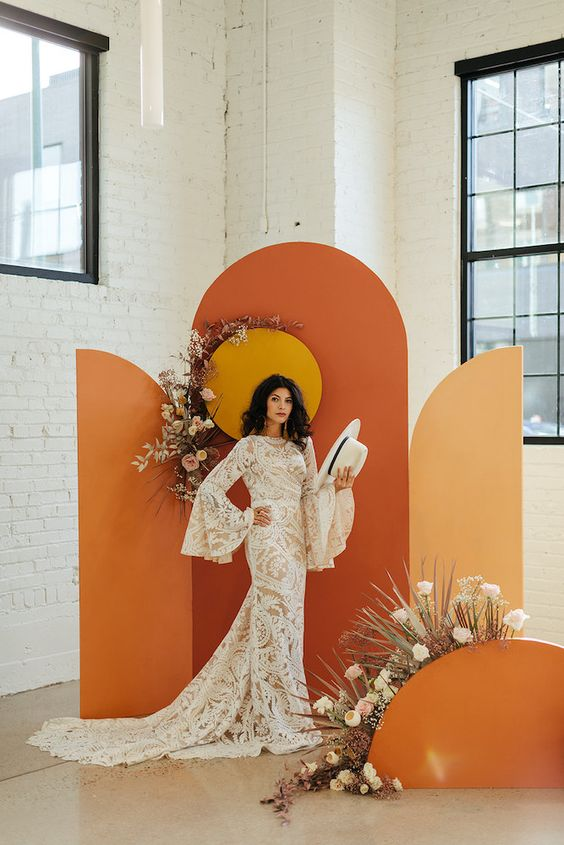 a chic 70s wedding backdrop with orange, rust and yellow parts, a sun and pastel and neutral florals and dried grasses