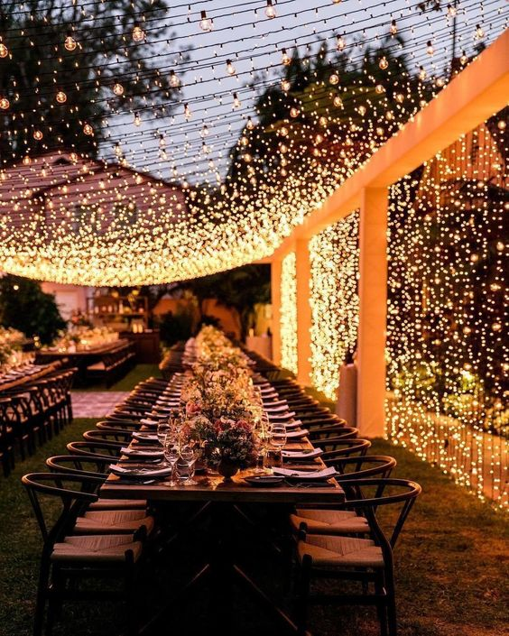 a chic and romantic outdoor wedding reception with a light canopy of warm lights is a very cozy and cool idea