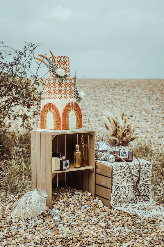 a jaw-dropping boho square wedding cake with geometric patterns and creative ruffle arches, with feathers and blooms