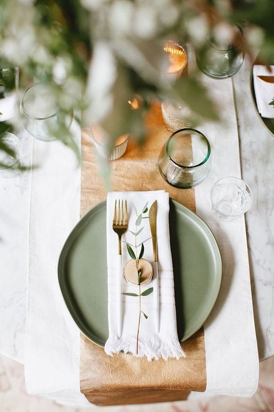 a lovely and fresh spring Scandinavian table setting with leather, neutral linens, green glasses and greenery