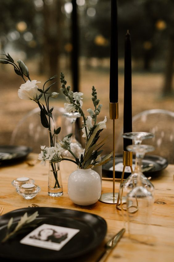 a moody cluster wedding centerpiece with sheer and white vases, black candles and white blooms, some greenery