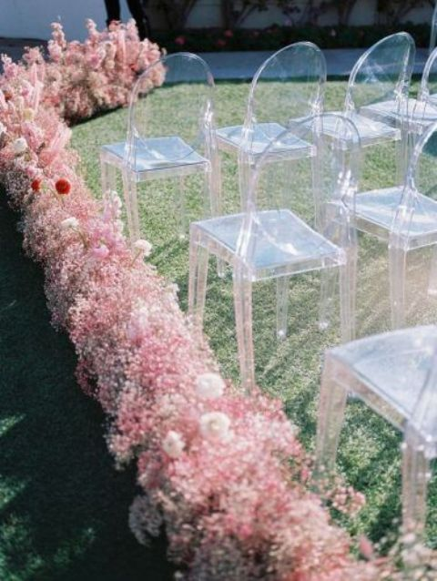 a pretty ceremony space with ghost chairs and a pink baby's breath line is a very bold modern idea for a wedding with a whimsy touch