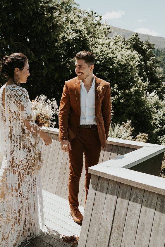 a rust-colored groom's suit with a white shirt and tan shoes for a stylish boho wedding in any season