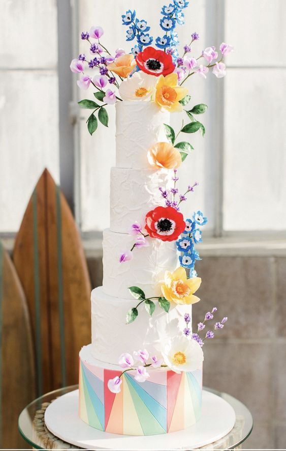 a white textural wedding cake with a geometric bright tier, colorful sugar blooms and leaves all over the cake