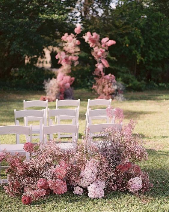 a ceremony space decorated with pink baby's breath and pink and blush blooms around is a very chic idea