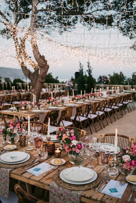 a colorful and bright wedding reception with bold florals, floral linens, candles and a warm light canopy over the space
