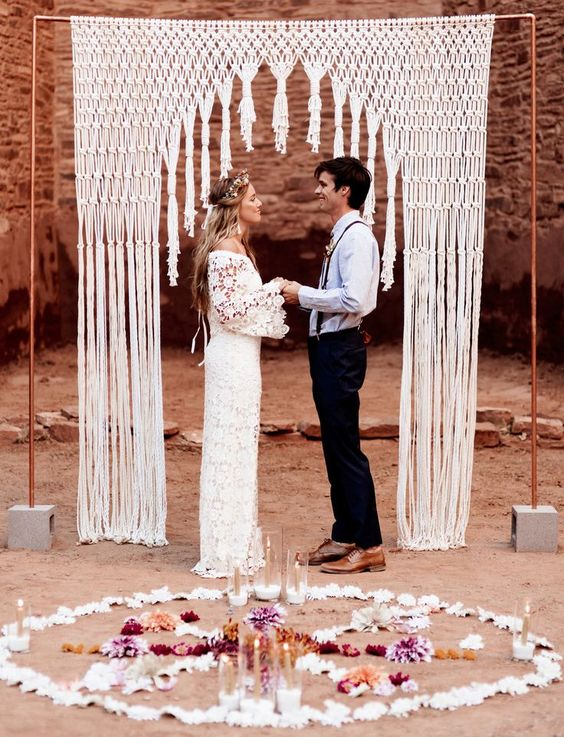 a cool boho wedding arch with a copper frame and macrame and fringe plus candles and blooms around
