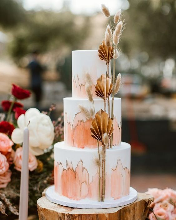 a jaw-dropping wedding cake with rust and gold abstract patterns, dried fronds and grasses is amazing