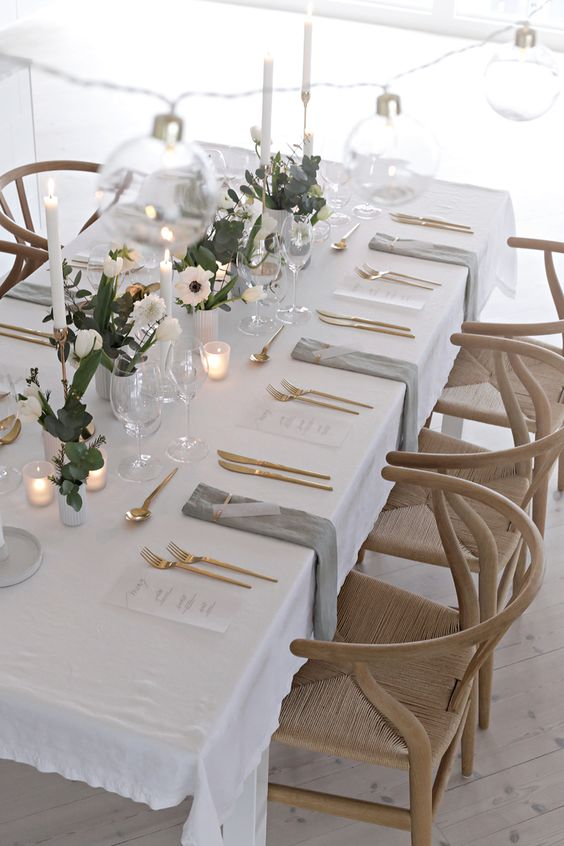 a lovely Scandinavian minimalist tablescape with greenery and white blooms, candles, gold cutlery and grey napkins