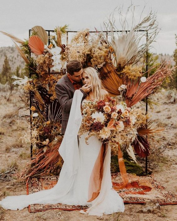 a lovely boho wedding backdrop with colored dried fronds, pampas grass, bold blooms and greenery is a cool idea for a boho wedding