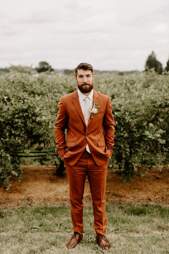 a rust-colored groom's suit, a white shirt and a creamy tie plus brown shoes for an elegant groom's look