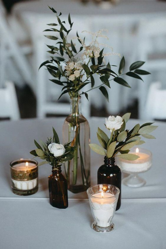 a simple and chic cluster wedding centerpiece of greenery and white blooms plus candles is an easy DIY piece
