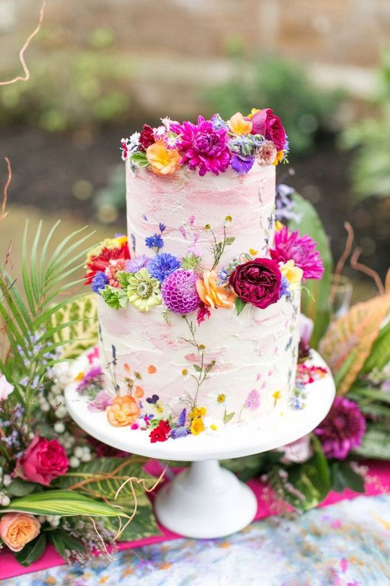 a white textural wedding cake with pink brushstrokes and super bold fresh blooms in all the shades of rainbow