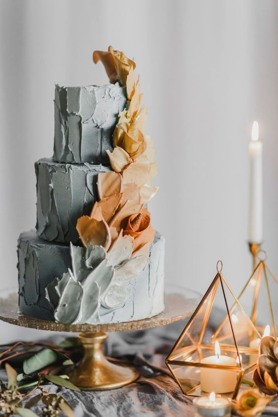 a winter wedding cake with textural tiers in pale blue with blue and tan brushstrokes is a very lovely and chic idea