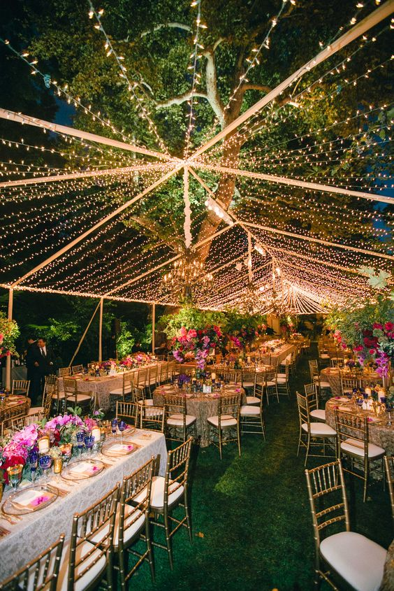 a colorful and glam wedding reception with a large light canopy over it plus additional chandeliers and lots of bright blooms