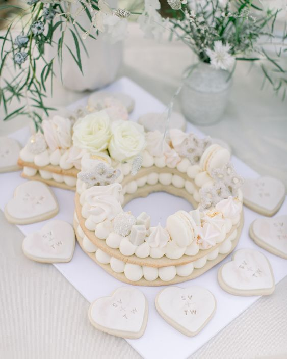 a cookie wedding cake topped with macarons, white blooms, beads and maringues plus matching cookies around