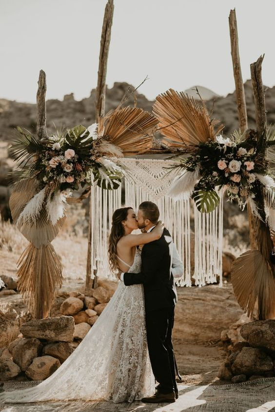 a lovely boho wedding arch with macrame and fringe, with pastel and white blooms, leaves, dried fronds and pampas grass