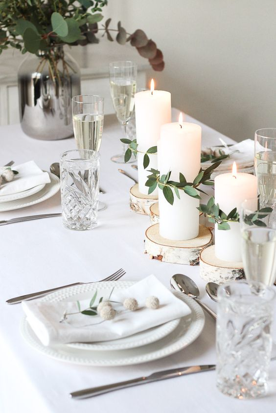 a minimalist and rustic Nordic wedding tablescape with wood slices and candles wrapped with eucalyptus, neutral porcelain and napkins