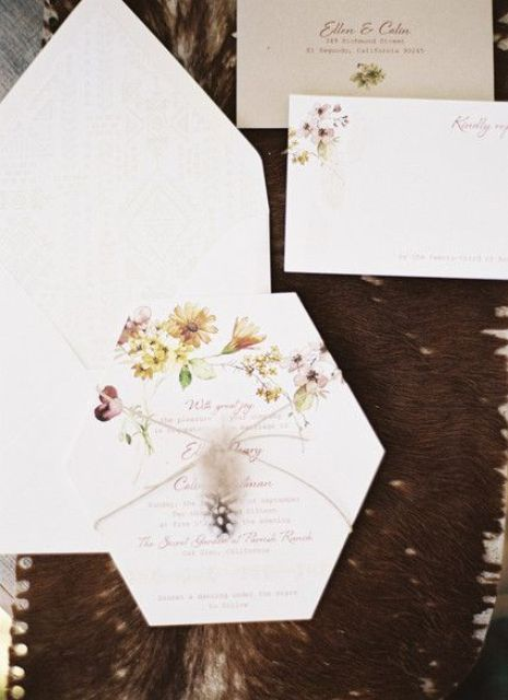 a pretty hexagon wedding invitation suite with floral printing and a feather plus a neutral envelope is chic