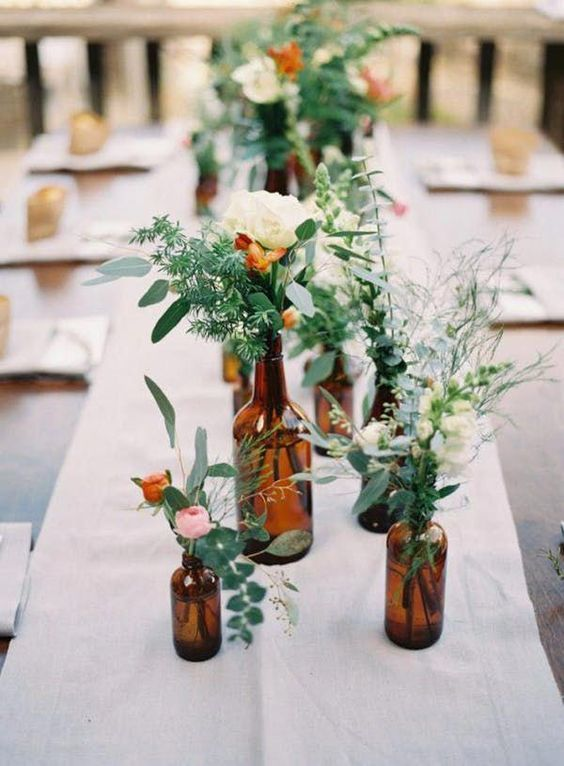 a simple cluster weddng centerpiece of dark bottles and greenery and neutral and pastel blooms is super chic