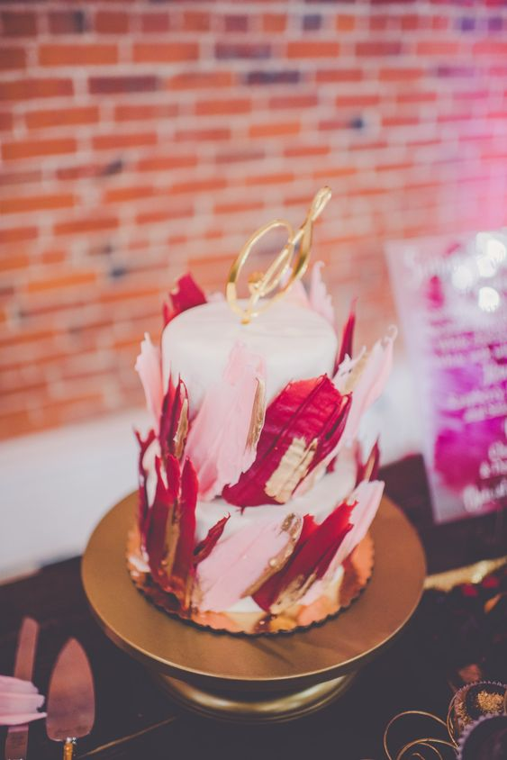 a white wedding cake covered with red and pink gilded brushstrokes and with a gold topper is all fun