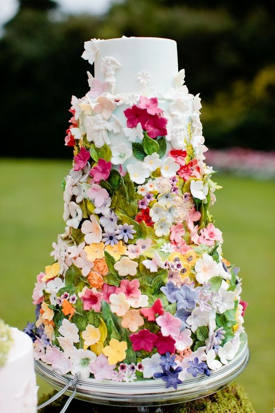 a white wedding cake fully covered with bold sugar blooms and leaves will be a nice solution for a fairy-tale or garden wedding