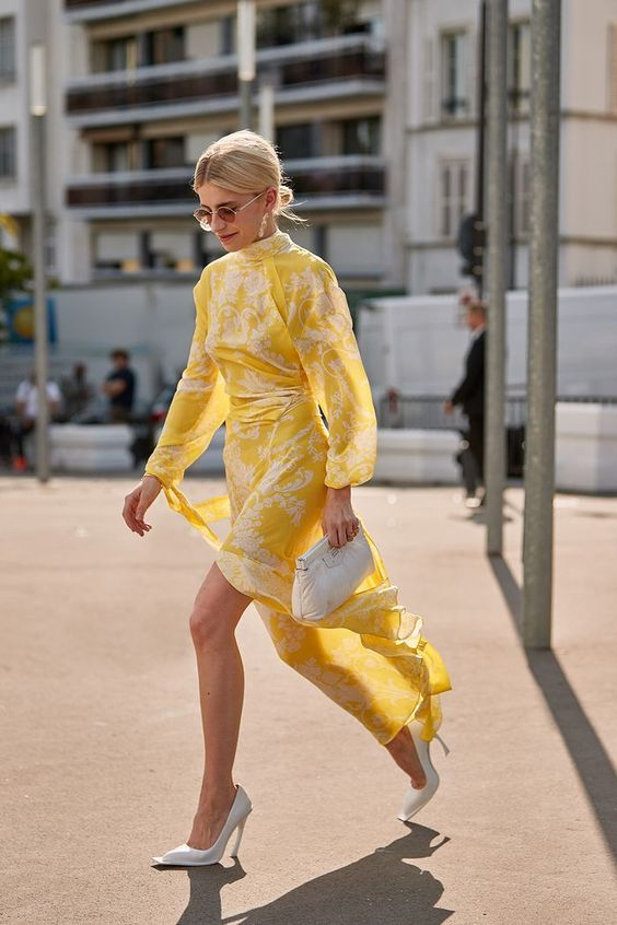a yellow and white patterned midi dress, white heels and a white clutch for a bold yet minimal look