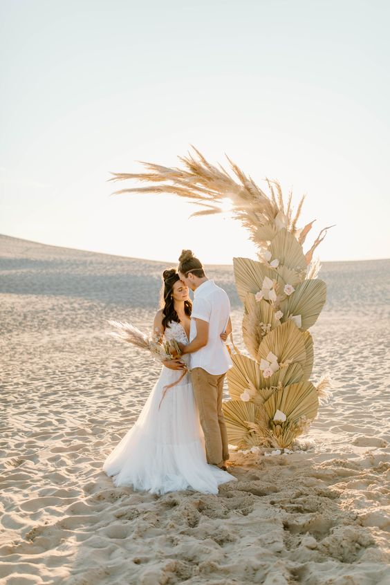 a boho beach wedding altar done with dried fronds, blush blooms and pampas grass is amazing and very dreamy for a boho beach wedding