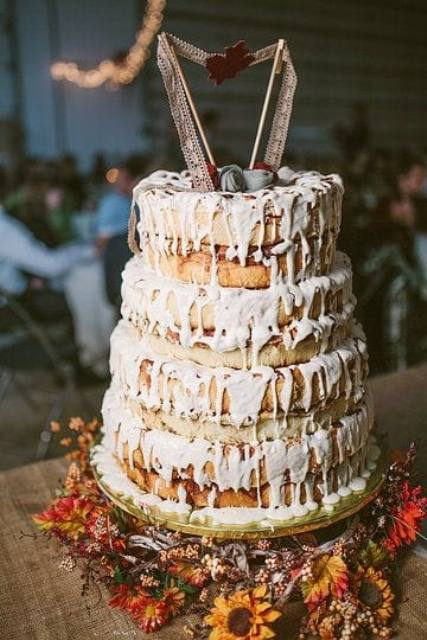 a cinnamon roll wedding cake with white icing, a pretty topper of ribbon and some fabric blooms for a boho wedding