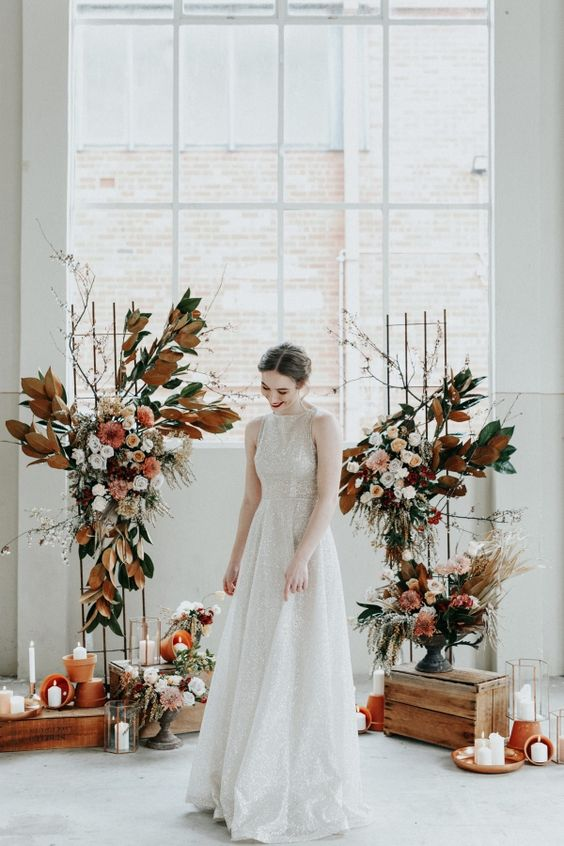 a creative wedding altar with rust and green leaves, blush, rust and white blooms, grasses, twigs, candles around