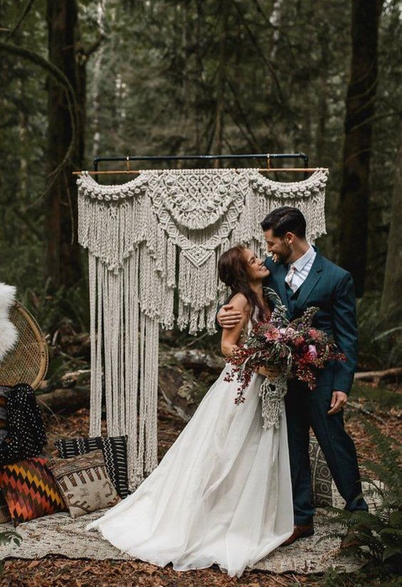 a macrame wedding arch with long fringe and lots of boho pillows around is a cool boho idea for a 70s wedding