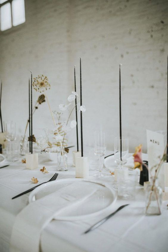 a minimalist Nordic tablescape with neutral linens, neutral porcelain, neutral candleholders and thin black candles, dried blooms