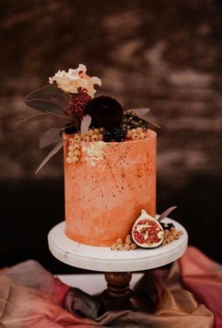 a rust textural wedding cake with gold leaf, fresh berries, blooms and dark foliage for a boho decadent wedding