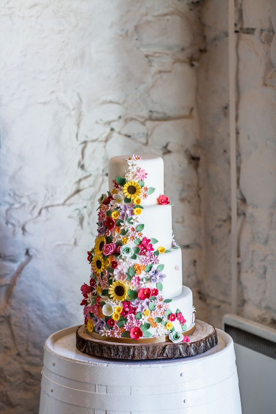 a whtie wedding cake with cool flowers