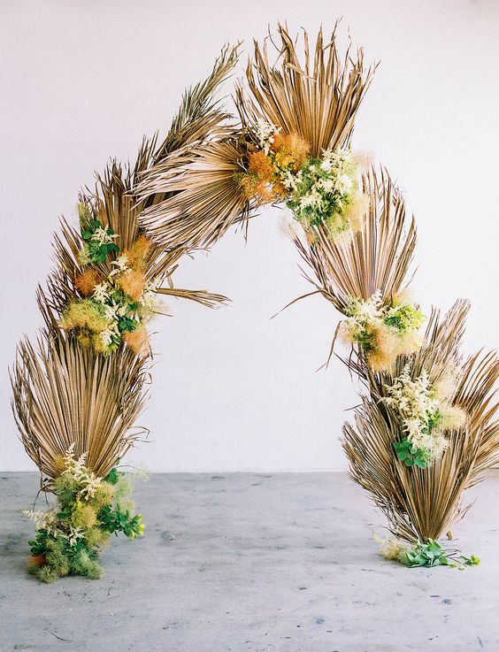 a boho tropical wedding arch of dried fronds, green and yellow blooms and leaves under the arch is pretty and cool