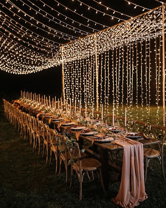 a fabulous wedding reception with candles, chairs with greenery, a pink runner and a light canopy over the space