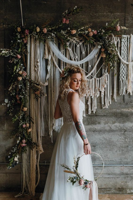 a macrame wedding backdrop with fresh greenery and pastel blooms attached to the wall for a 770s boho wedding