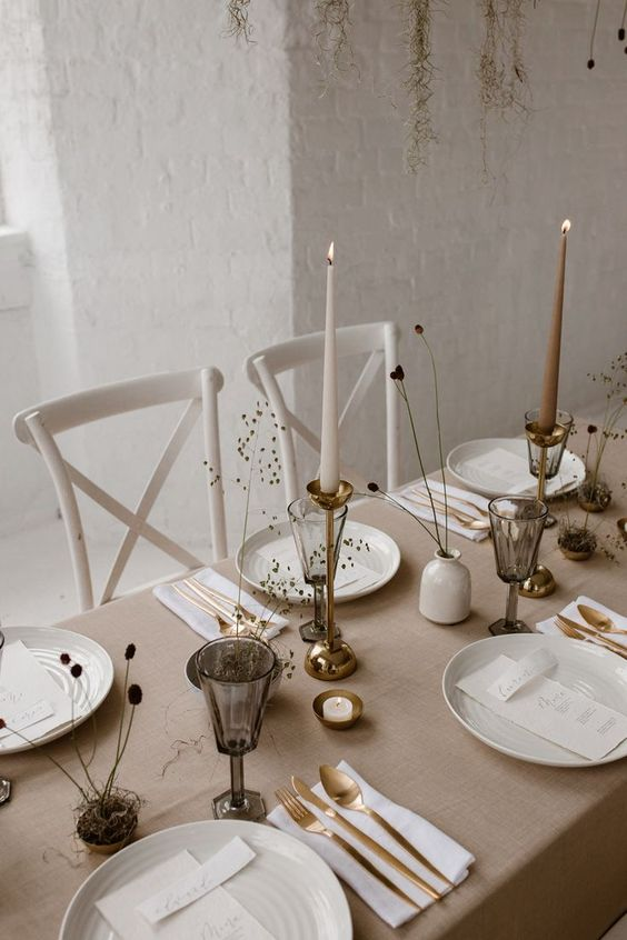 a minimalist Scandinavian table setting with neutral linens, candles, smoked glasses, gold cutlery, dried blooms